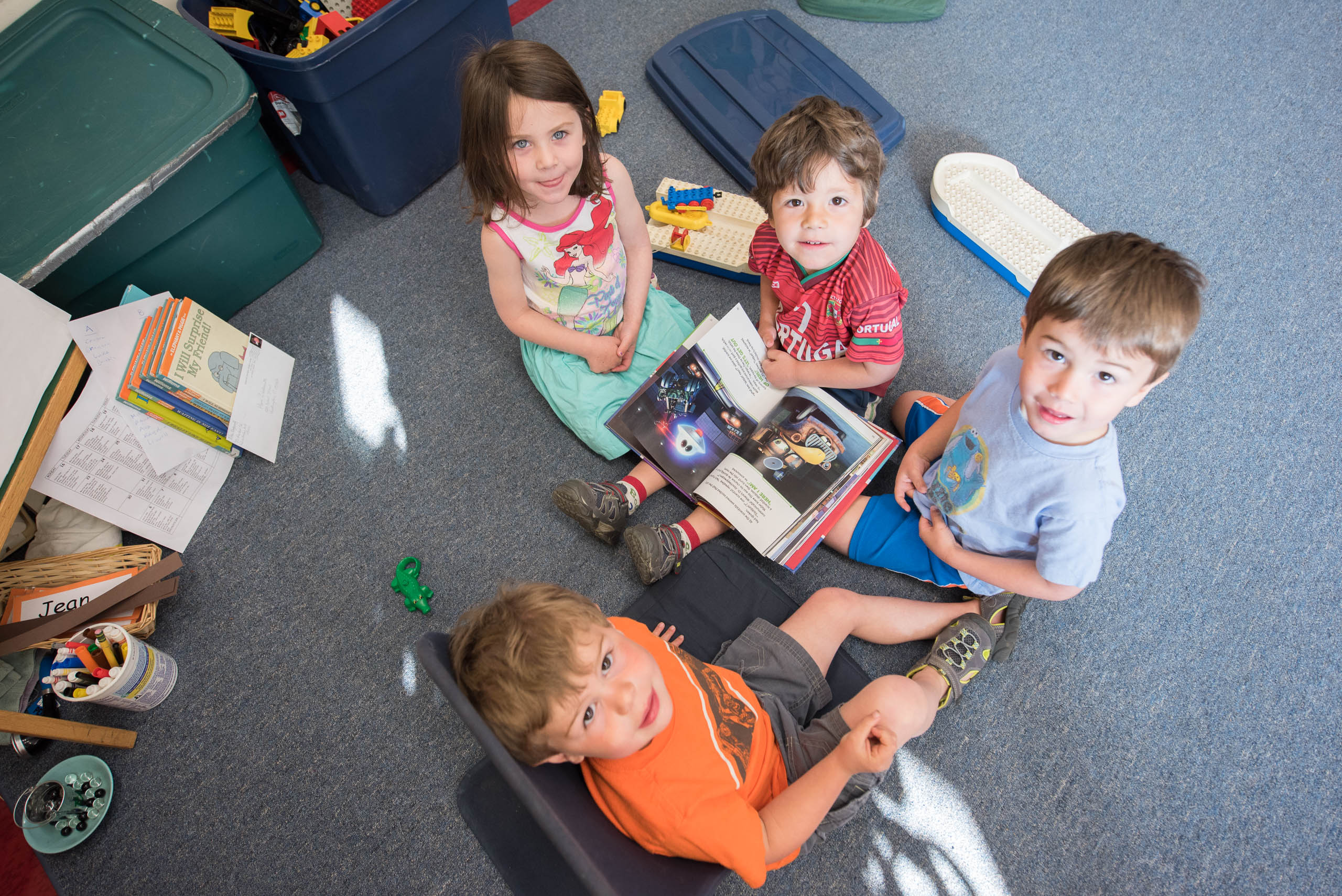 image of four kindergarten students reading a book